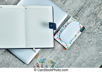 Open notebook, laptop, mouse, clips and a cup of tea on wooden desk