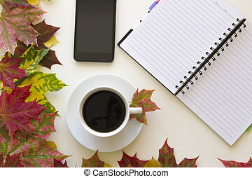 Open notebook, mobile phone and cup of coffee, framed with autumn leaves on white background. Flat lay. Top view. Empty copy space for text