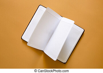Open notebook on a yellow background, top view