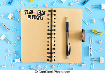 Open notebook on springs with an inscription To Do List. Stationery razrosannye on a blue background. Clerical buttons, paperclips and asterisks are in disarray.