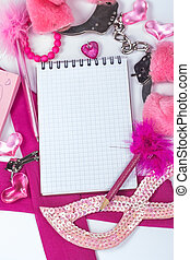 open notebook surrounded pink baubles