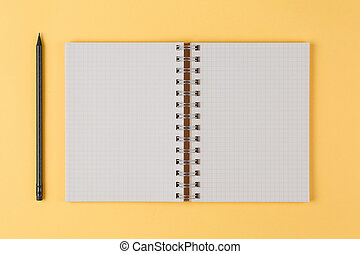 notebook with a black pencil on yellow background top view