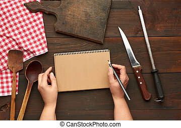 open notebook with blank brown sheets and kitchen utensils on a brown wooden table