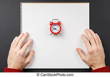 notebook with red alarm clock in hands
