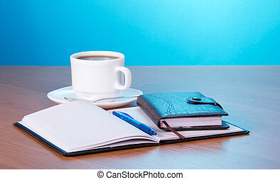 Open notepad and cup of coffee