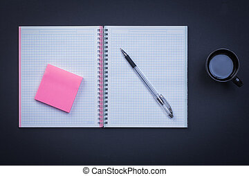 Open notepad pen sticky note and cup of coffee on black backgrou