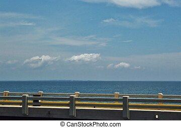 Open ocean and sky with bridge