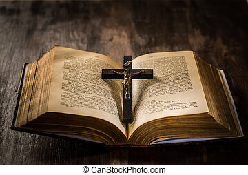Open old bible with crucifix