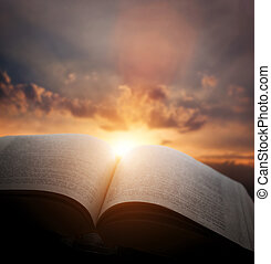Open old book, light from sunset sky, heaven. Education, religion concept