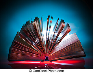 Open old book, mystical light at background
