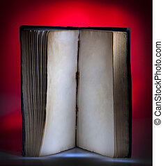 Open old book, mystical red light at background