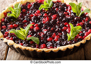 open pie with summer berries is decorated with peppermint close-up in a baking dish. horizontal