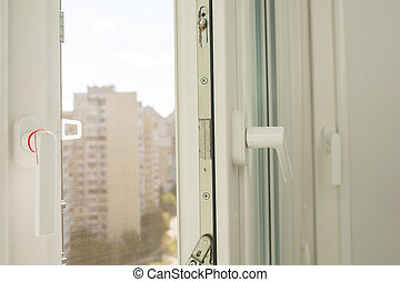 Open plastic window with a view of multi-storey apartment buildings in sunny day