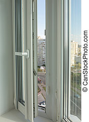 Open pvc window on the background of multi-storey apartment buildings
