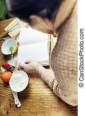 Open recipe book in the hands of an elderly woman