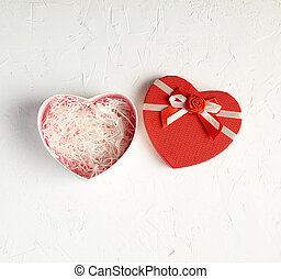 open red heart-shaped gift box with a bow on a white background,