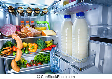 Open refrigerator filled with food. Focus on Bottles of milk...