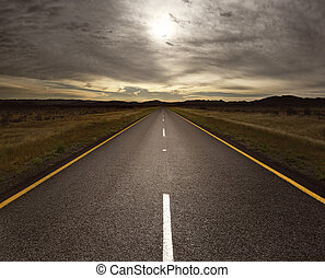 Open road leading into the light - Straight tar road leading...