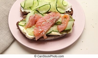 Open sandwich with fish and vegetables with pink ceramic...