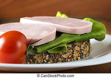 Open sandwich with ham, green salad and one tomato on plate