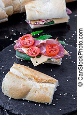 Open sandwich with jamon, arugula, tomatoes, cheese on stone slate black background. Close up