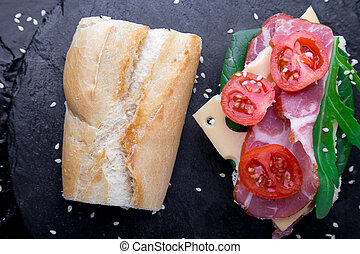 Open sandwich with jamon, arugula, tomatoes, cheese on stone slate black background. Top view