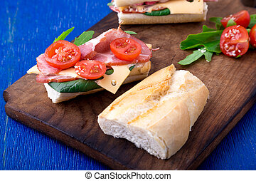 Open sandwich with jamon, arugula, tomatoes, cheese on wooden board blue background. Rustic.