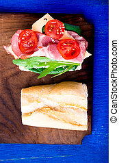 Open sandwich with jamon, arugula, tomatoes, cheese on wooden board blue background. Rustic. Top view.