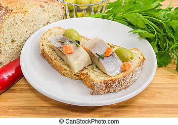 Open sandwich with pickled herring fillet among of some ingredients