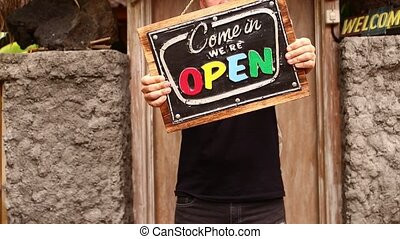 Open sign board in a man hands on a tropical nature background. Shooted on Bali island, full HD.