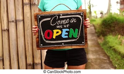 Open sign board in a woman hands on a tropical nature background. Shooted on Bali island, full HD.