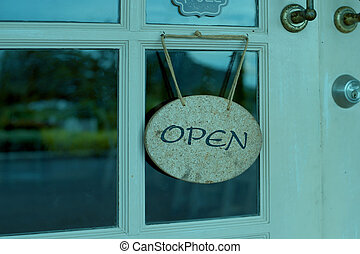 open sign hanging in front of shop window