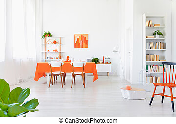 Open space area of white and orange colored living room interior in modern home.