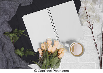 Open spiral notebook with blank pages on wood background.