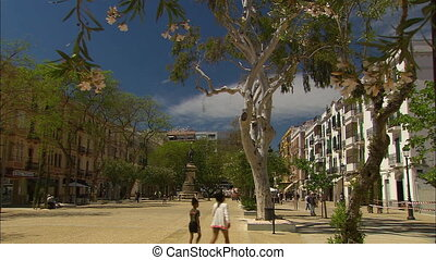 Wide low-angle sunny day still shot of an open residential street with unique trees, three storey apartment buildings, and a historical monument far ahead. People walk leisurely along the open space, Ibiza Balearic , Spain