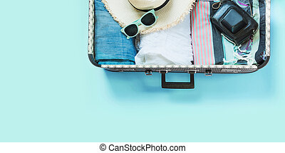 Open suitcase with female clothes for trip on pastel blue. Top view with copy space. Summer concept travel.