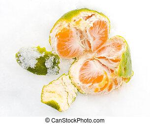 Open tangerine on snow