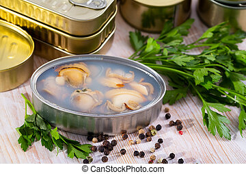 Open tin can with sea clams in its own juice