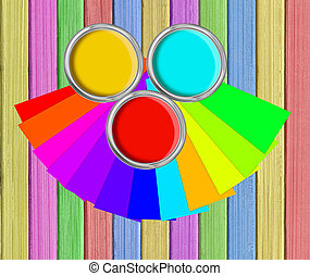 open tin cans with paint and palette on painted wooden planks background