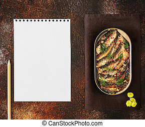 Open tin of Baltic sprats in oil with spices with a sheet of white writing paper and pencil on an old brown background