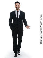 Open to new ideas. Full length of handsome young man in full suit holding one hand in pocket and looking at camera while standing against white background