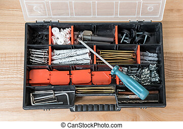 Open toolbox with different instruments. Screws and screwdriver Plactic box with tools on wooden background. Furniture assembly and renovation work concept.