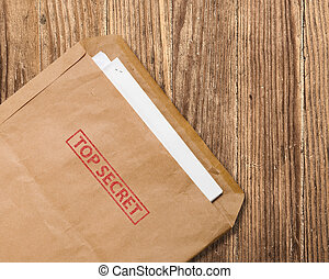 Open top secret envelope on table. - Open yellow envelope...