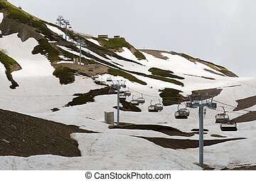 open-type cable car over snow-covered mountains on a summer day
