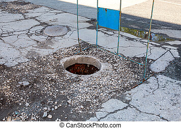 Open unsecured sewer manhole on the asphalt road