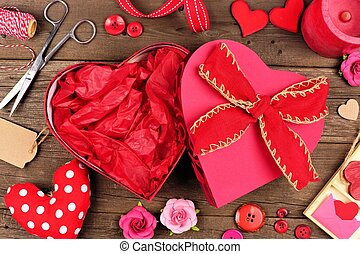 Open Valentines Day heart shaped gift box with frame against wood