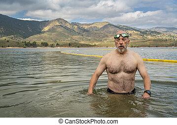 open water swimming in mountain lake - active senior man ...