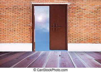 Open wood door on brick wall with blue sky