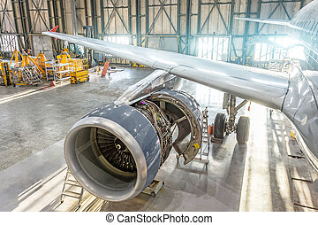 Opened aircraft engine in the hangar, maintenance. Wing view