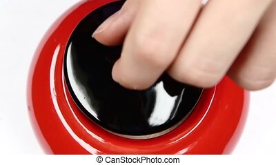 Opened and closed red jar with sugar, using spoon, on white, slow motion